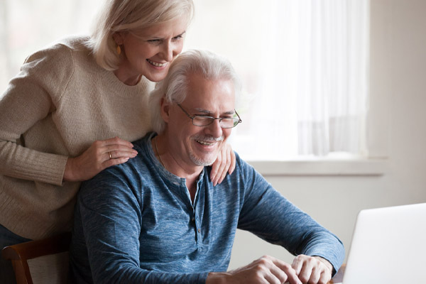 happy couple using laptop to search for air conditioner replacement company